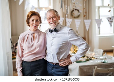 Senior couple standing indoors in a room set for a party. Copy space.