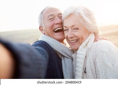 Senior Couple Standing On Beach Taking Selfie
