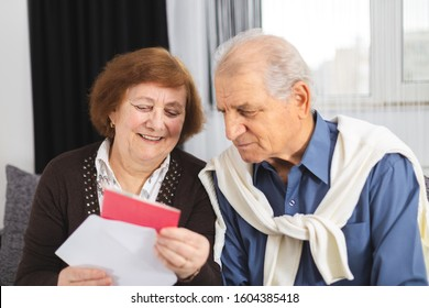 Senior couple standing on the couch and reading a letter received. Portrait Of A Happy Senior Couple At Home Reading Paper
