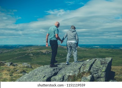 A senior couple are standing on a rock in the moor in summer