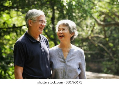 Senior couple standing side by side, smiling