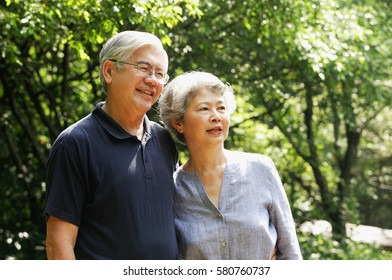 Senior couple standing side by side, looking away, smiling