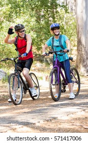 Senior couple standing with their bike in a forest
