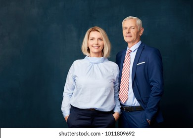 Senior couple standing together at dark background. Beautiful blond woman looking at camera and smiling while elegant old man standing next to her.