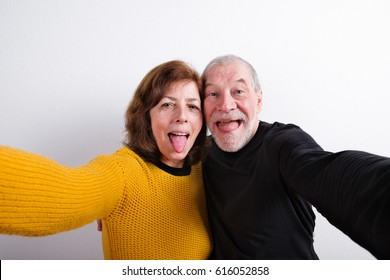 Senior couple sticking tongues out, taking selfie. Studio shot.