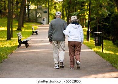 Senior couple strolling down a garden path together