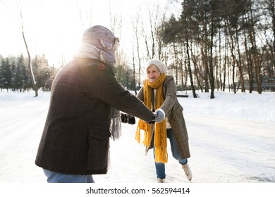 Senior couple in sunny winter nature ice skating.