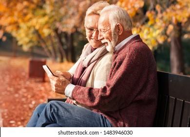 Senior couple with tablet sitting on bench. Sunny autumn park.