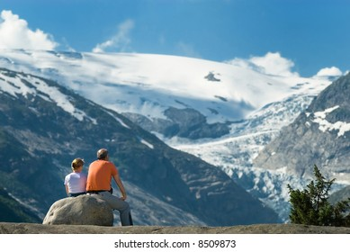 Senior couple taking a rest in front of a spectacular snow-capped mountain