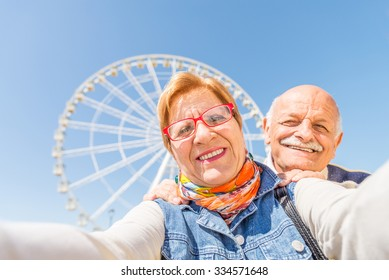 Senior couple taking a selfie at amusement park - Two persons in the 60's having fun with new technologies outdoor