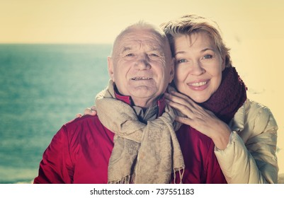 Senior couple taking walk by sea on sunny chilly day