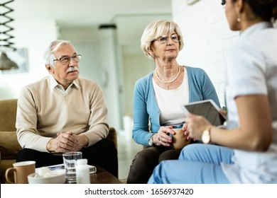 Senior couple talking to healthcare worker during home visit. Focus is on senior woman.
