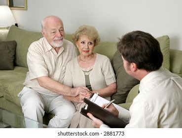 A senior couple talking with a marriage counselor.  Could also be a salesman in their home.