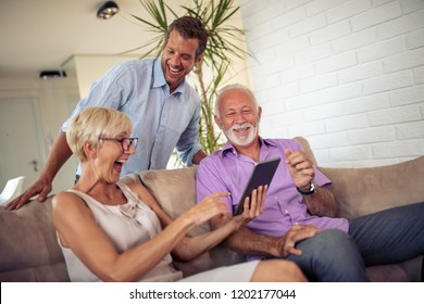 Senior couple with their son using digital tablet at home.