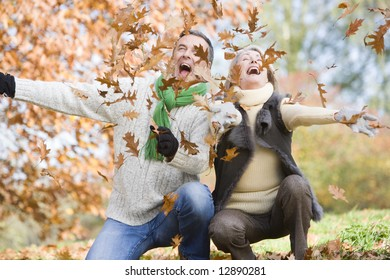 Senior couple throwing autumn leaves in the air