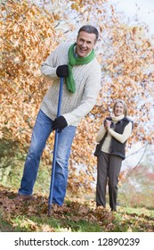 Senior couple tidying autumn leaves in garden