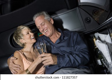 Senior couple toasting in a limousine