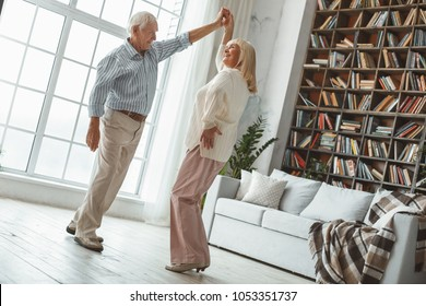 Senior couple together at home retirement concept dancing active dance twist