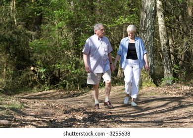 Senior couple together on a summerday strolling through the park