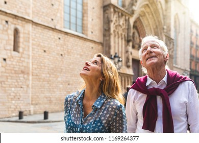 Senior couple of tourists visiting the old town in Barcelona. Adult woman and man looking up at some beautiful architecture on a sunny day in Spain. Travel and tourism concepts