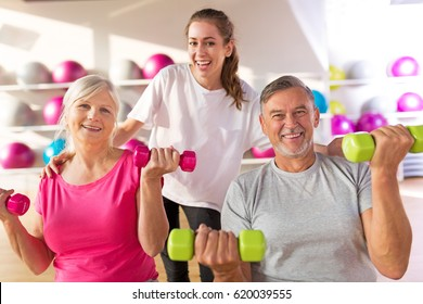 Senior couple training in the gym with a personal trainer