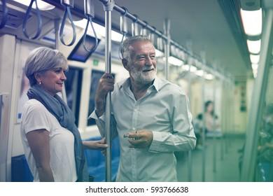 Senior couple traveling inside train subway