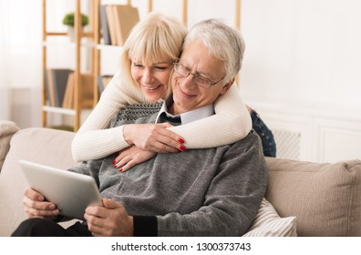 Senior couple using digital tablet, having video call in the living room