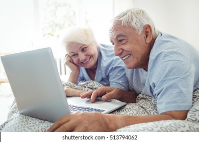 Senior couple using laptop in bedroom