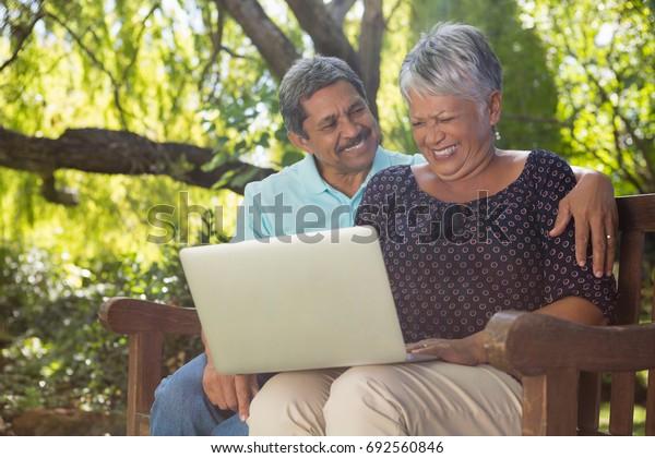 Senior couple using laptop in the garden