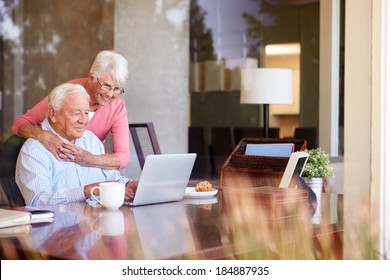 Senior Couple Using Laptop On Desk At Home