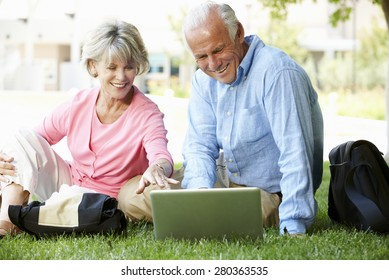 Senior couple using laptop outdoors
