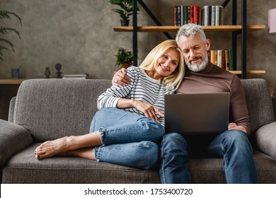 Senior couple using laptop and smiling while resting on couch at homewhile watching movie