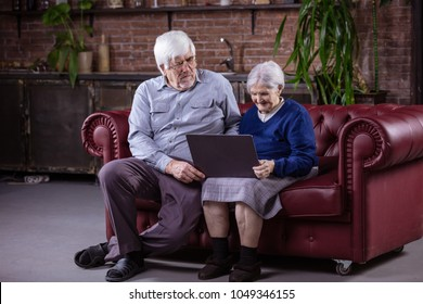 Senior couple using laptop while sitting on couch