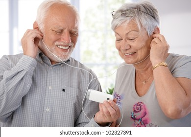 Senior couple using mp3, listening to music, smiling.