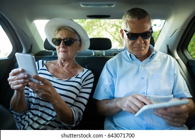 Senior couple using technologies while sitting in car