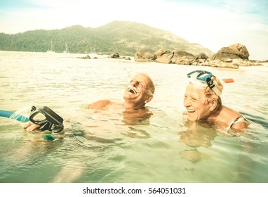 Senior couple vacationer having genuine fun on tropical Koh Lipe beach in Thailand - Snorkel tour in exotic scenario - Active elderly and travel concept around world - Warm desaturated greenery filter