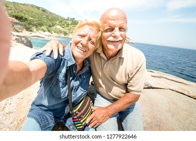 Senior couple vacationer taking selfie while having genuine fun at Giglio Island - Excursion tour in seaside scenario - Active elderly and travel concept around the world on warm bright sunny filter