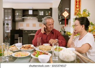 Senior couple waiting for their children and grandchildren for Chinese New Year dinner. Scrolls wishing luck and wealth in the background