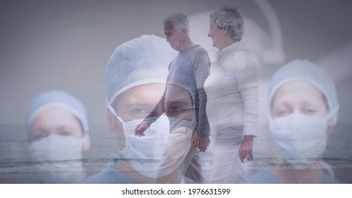 Senior couple waking on the beach against portrait of team of surgeons wearing face masks. healthcare and medical professionalism concept