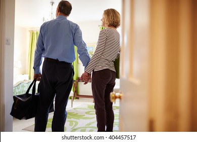 Senior couple walk in to hotel room holding hands, back view