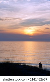A senior couple walk togetehr along the beach by a shiny, silvery sea reflecting a colorful sunset