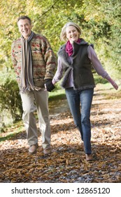 Senior couple walking along path in autumn woods