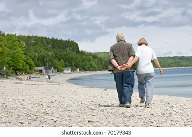 A senior couple walking along the shores of a rocky beach, backs to the camera, with plenty of copy space.