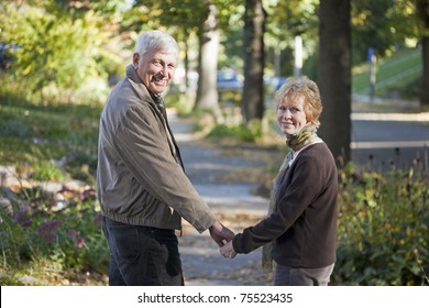 Senior couple walking along the sidewalk looking back at the camera