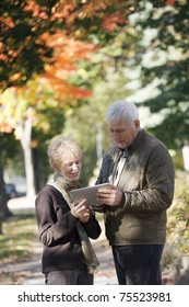 Senior couple walking along the sidewalk looking at their digital tablet