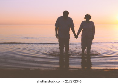 Senior couple walking along the water holding hands
