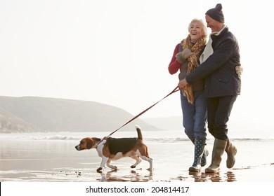 Senior Couple Walking Along Winter Beach With Pet Dog