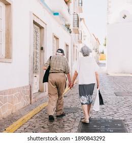 senior couple walking down the street holding hands