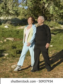 senior couple walking exercise outdoors in woods