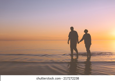Senior couple walking holding hands at sunset